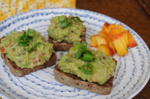 open face rye bread avocado sandwich and diced peaches