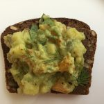 Slice of rye bread with guacamole and dill