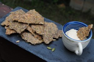 rye seed crackers with cup of hummus