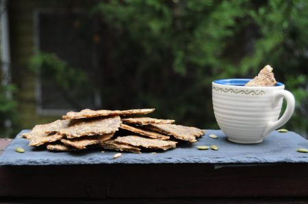 seed crackers on the tray with cup on hummus